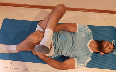 Man performing sciatica stretch exercise when muscle is taken to end point and stretched