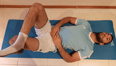 Man performing sciatica exercises and stretching the right glute muscle
