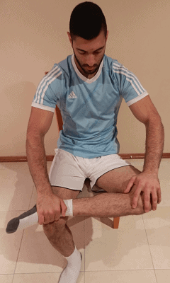 Sciatica exercise with man pushing down on left knee to stretch muscle in hip
